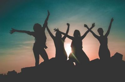 women-silhouette-against-sunset-with-arms-raised-in-the-air